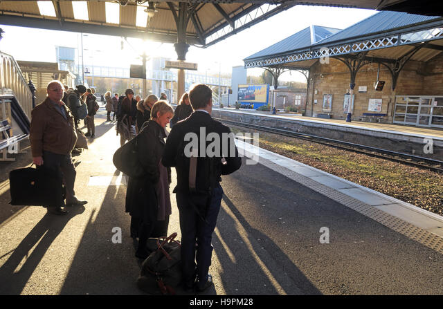 Passengers casting shadows on a railway platform, Perth,Scotland,UK - Stock Image