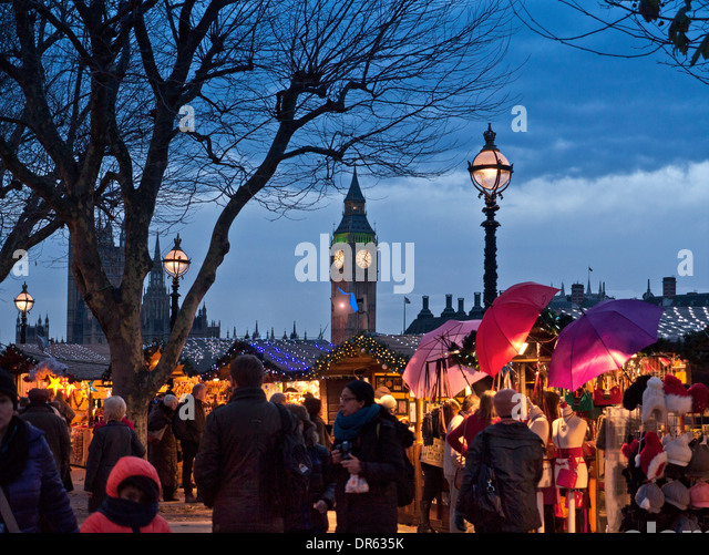South Bank Christmas market stalls and shoppers with Houses of Parliament behind at dusk London UK - Stock Image