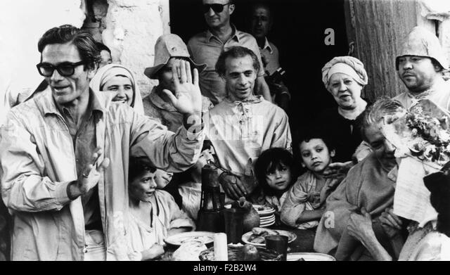 Italian film maker Pier Paolo Pasolini, directs villagers appearing as extras in 'Decameron'. He was filming - Stock Image