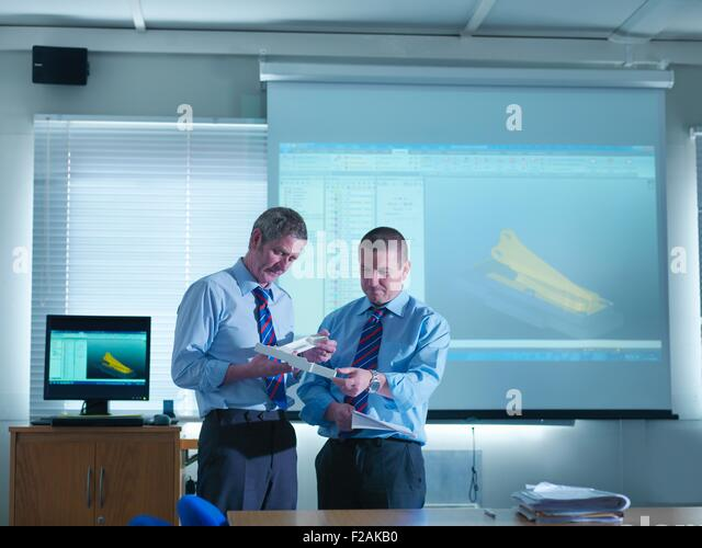Engineering designers with CAD images on screen in engineering factory - Stock Image
