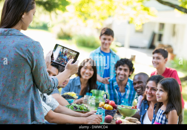 Adults and children posing for a photograph at a summer party. - Stock Image