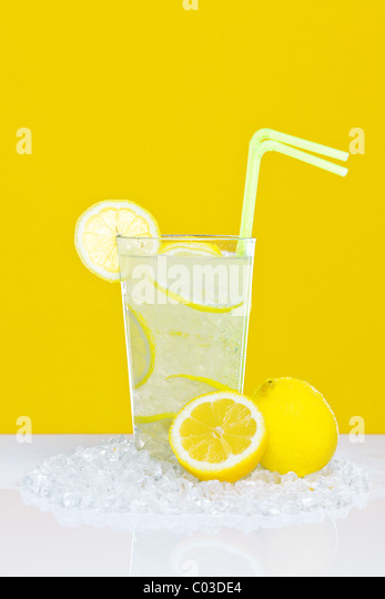 Photo of traditional lemonade in a glass with crushed ice and lemon slices, on a white table with yellow background. - Stock Image