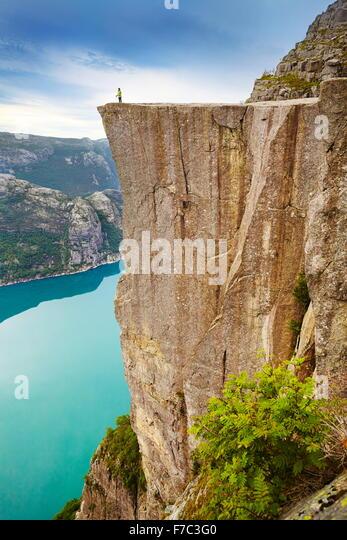Single tourist on the Pulpit Rock landscape, Preikestolen, Lysefjorden, Norway - Stock Image