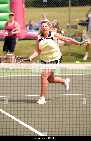 Elderly woman taking part in a charity tennis event, Headley, Hampshire, UK. - Stock Image