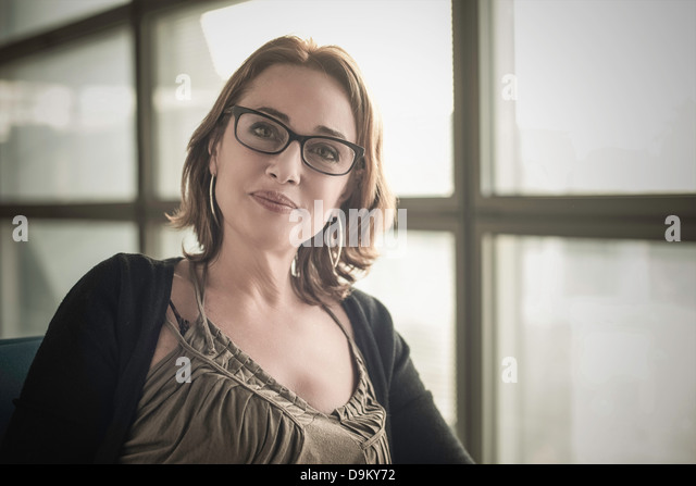 Portrait of mature woman wearing glasses looking at camera - Stock Image