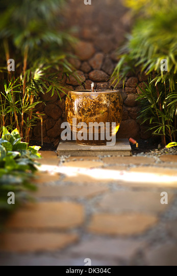 Stone path and water fountain in tranquil tropical garden - Stock Image