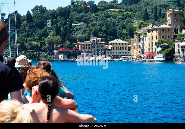 tourists on a boat trip arriving at portofino on the italian riviera. - Stock Image