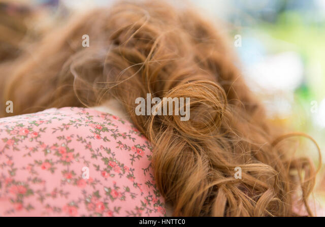 The rear of a red haired girl - Stock Image