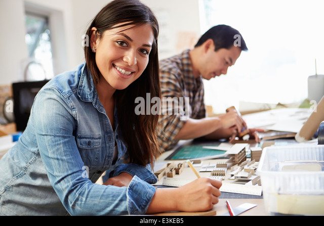 Female Architect Working On Model In Office - Stock Image