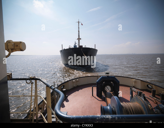 Tugboat pulling ship in ocean - Stock Image