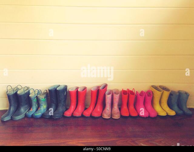 A row of children's colorful rain boots. - Stock-Bilder