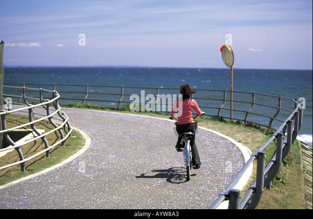Woman on a bicycle by the sea - Stock-Bilder