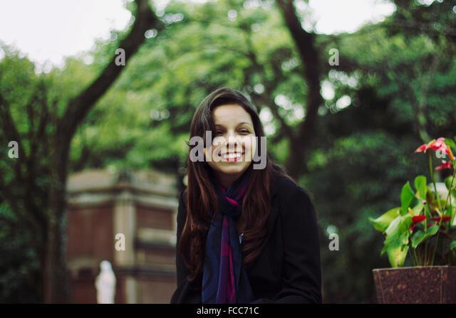 Smiling Teenage Girl Looking Away Against Trees - Stock-Bilder