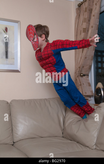 three year old boy dressed up as spiderman and jumping on furniture. - Stock Image
