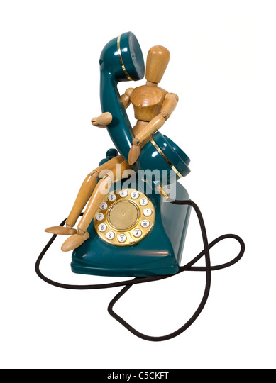 Traditional desk phone with rotary dial held by a model taking a call - path included - Stock Image