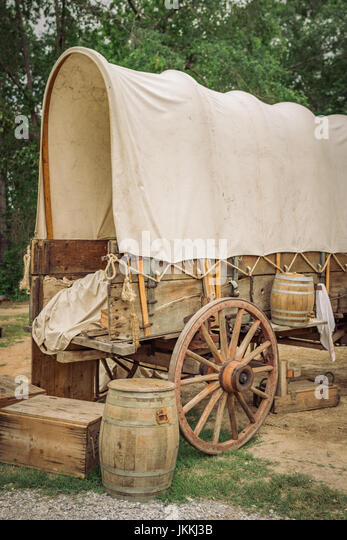 Restored old historic covered wagon also know as a conestoga wagon with wooden boxes and barrels. - Stock Image