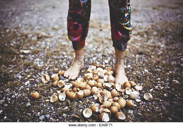 Low section shot of woman walking on eggshells - Stock Image