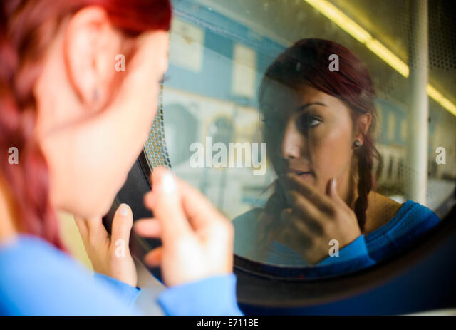 Young woman in laundromat, looking at reflection in washing machine - Stock Image