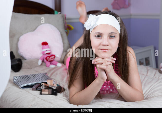 portrait of a girl lying on her bed with make-up - Stock Image