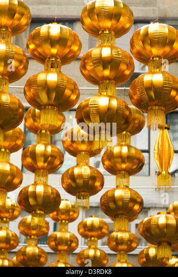 Gold Chinese New Year ornaments hang above a street in Hong Kong - Stock Image