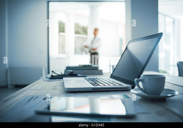 Businessman standing with arms crossed in his office, desktop with laptop on foreground, selective focus - Stock Image