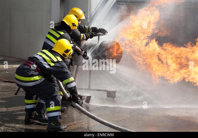 firefighters attack a propane fire during a training exercise - Stock Image