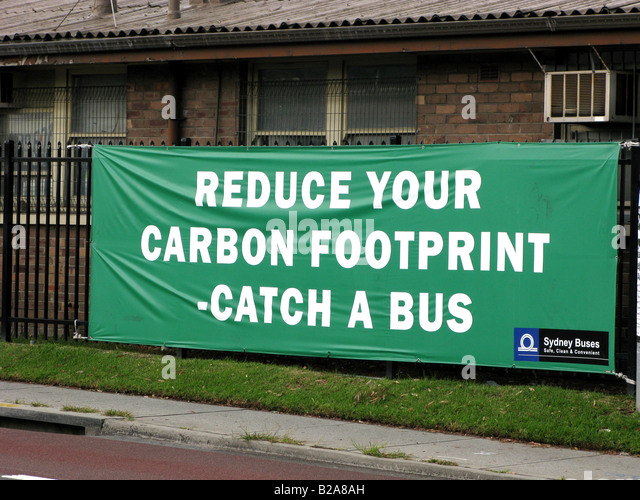 A sign urges commuters to use buses for transport in order to reduce their carbon footprint - Stock Image