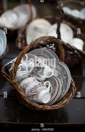 saucer and cups at flea market. wicker basket, crockery, second hand, market. - Stock Image