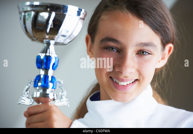 Smiling girl holding fencing trophy - Stock Image