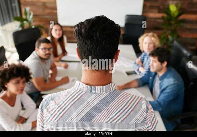 Rear view portrait of man giving business presentation to colleagues in conference room.  Young people meeting in - Stock Image