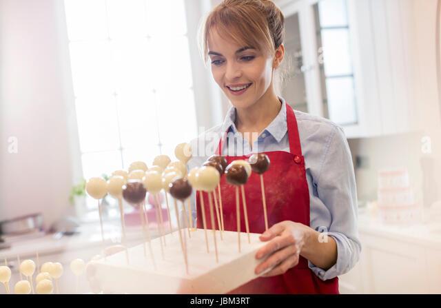 Smiling female caterer baking cake pops in kitchen - Stock-Bilder