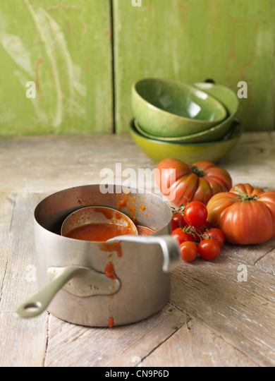 Saucepan of tomato soup on table - Stock Image