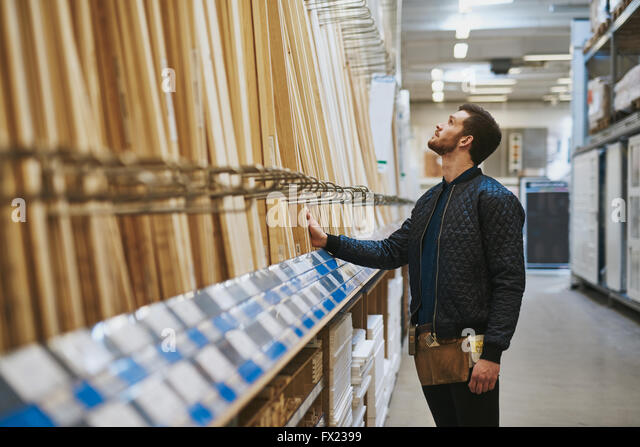 Carpenter selecting wood in a hardware store or warehouse standing looking at cut lengths on a rack, side view - Stock Image