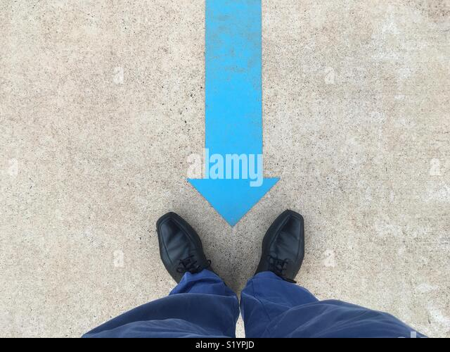 A blue arrow painted on the ground pointing to a man's black shoes and blue pants. - Stock Image