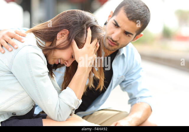 Side view of a muslim man comforting a sad caucasian girl mourning in a train station - Stock Image