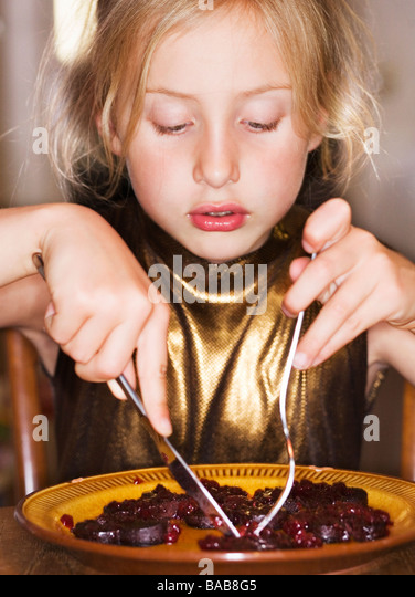A girl eating food. - Stock Image