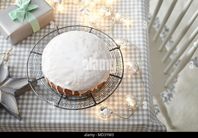 Iced cake on table with decorative lights - Stock Image