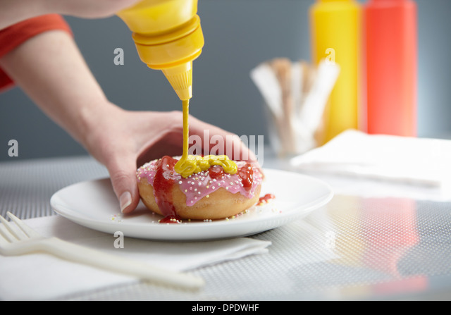 Woman squirting donut with ketchup and mustard - Stock Image