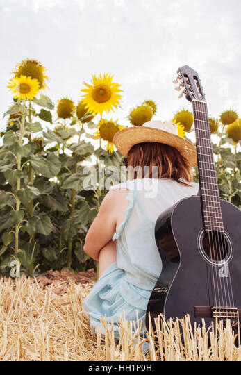 Young woman in summer with her black guitar in front of a lot of sunflowers - Stock Image