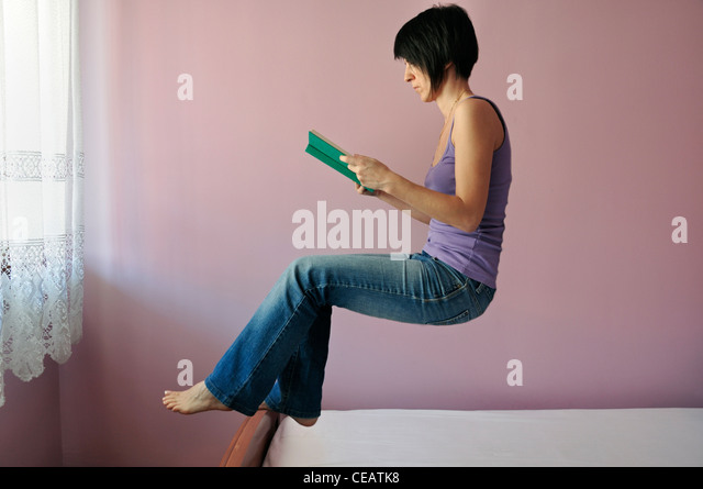 Woman floating reading book - Stock Image