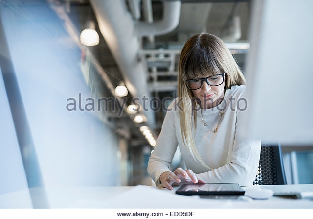 Businesswoman using digital tablet at office desk - Stock Image
