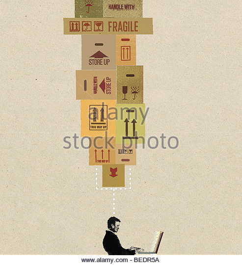 Businessman on laptop with head connected to cardboard boxes - Stock Image