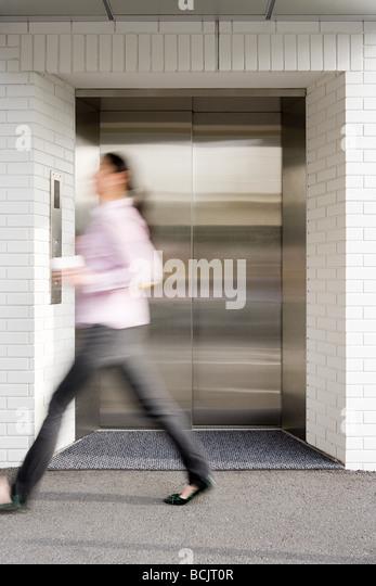 Blurred woman walking past elevator - Stock-Bilder