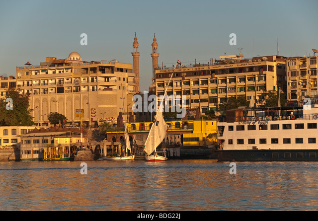 Feluccas two traditional wooden sailboat on Nile River Aswan Egypt with minarets from Islamic mosque in backgground - Stock Image