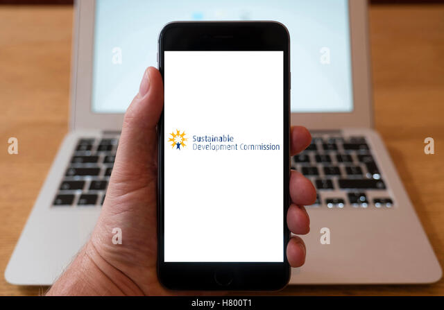 Using iPhone smartphone to display logo of the Sustainable Development Commission - Stock Image