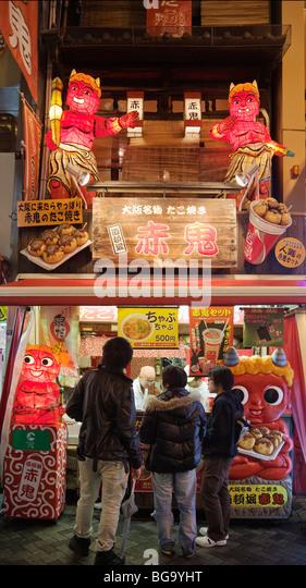 A stand selling Takoyaki (octopus dumplings) in Dotonbori canal district, Osaka, Japan - Stock Image