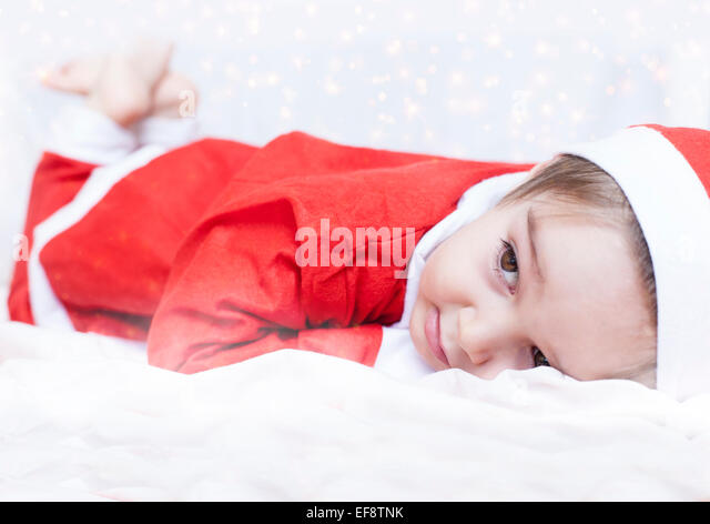 Boy dressed as Santa Claus lying on bed - Stock Image