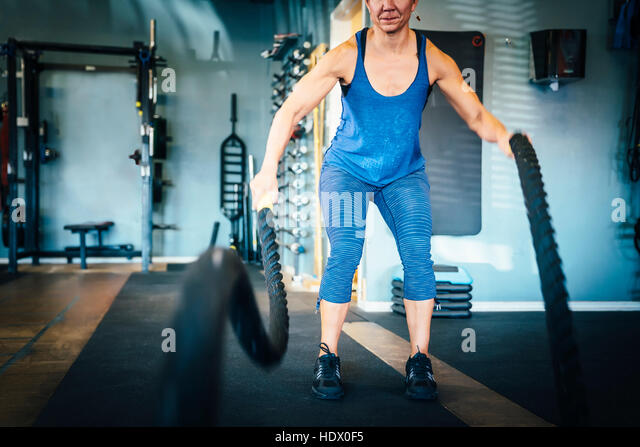 Caucasian woman using ropes in gymnasium - Stock Image