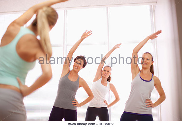 Women with arms raised in exercise class - Stock Image