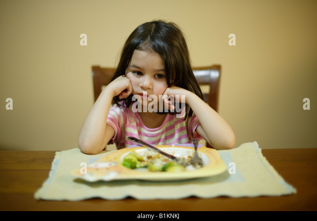 Girl aged four reluctant to finish the vegetables on her plate of Sunday roast dinner - Stock Image